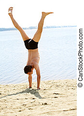 Equilibrium - Skilled guy standing on arms on sand with...