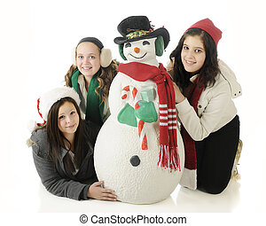 Teens with Christmas Snowman - Three young teens happily...