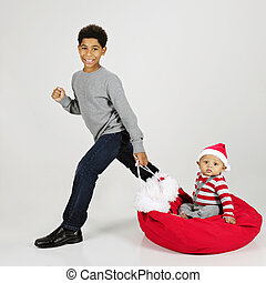 Santa Bag Ride - An elementary boy happily taking his baby...