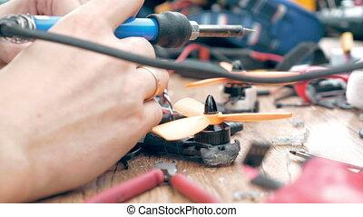 Man's hands welding details assembling FPV drone - Close up...