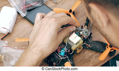 Man assembling FPV drone using tools, preparing quadcopter...