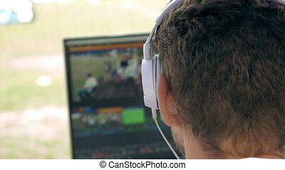 Video broadcast editor with headphones against screen -...