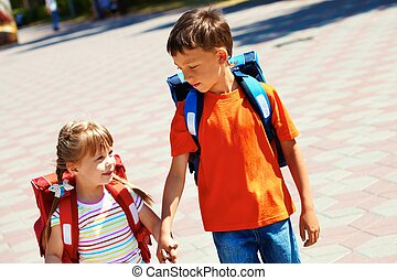 Beginners - Portrait of smart friends with backpacks walking...