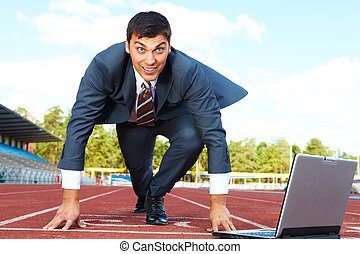 At start - Image of businessman getting ready for race with...