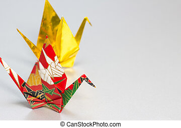 Origami cranes made of gold and colorful Japanese patterned...
