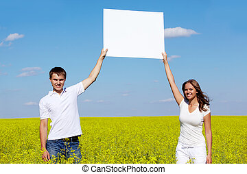 Advertisers - Portrait of happy guy and girl with blank...
