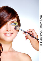 Doing makeup - Close-up of gorgeous female with bright...