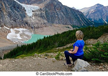Woman sitting on stone in frone of lake. - Alberta. Canada.