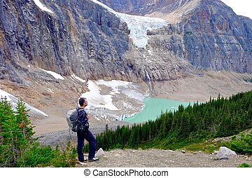 Man hiker stainding on rocks by glacier lake. - Rocky...