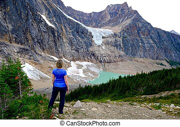 Woman standing on rocks by glacier lake. - Candian Rockies....
