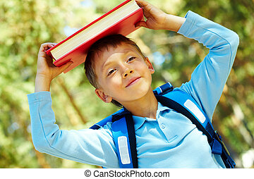 Knowledge - Photo of diligent schoolboy with book on his...