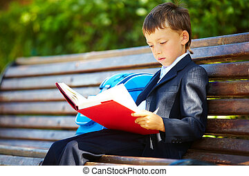 After school - Portrait of smart boy sitting in the park and...