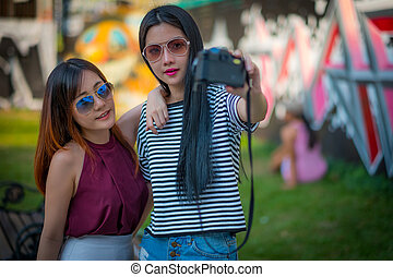 The tourism, travel, leisure, holidays and friendship concept - smiling teenage girls with camera outdoors