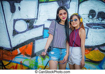 The tourism, travel, leisure, holidays and friendship concept - smiling teenage girls with camera outdoors,And fashion sunglasses.