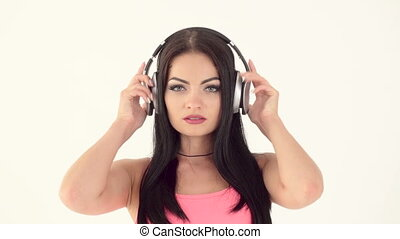 woman listening to music on headphones - beautiful brunette...