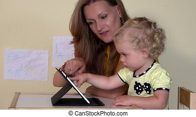 Babysitter teaching little child girl using tablet computer....
