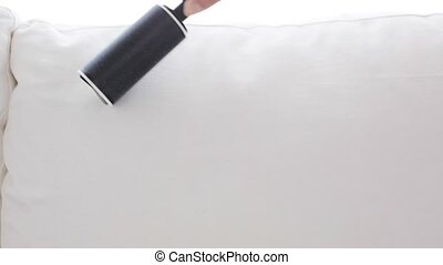 woman with sticky roller cleaning sofa upholstery - people,...