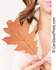 Autumnal girl with oak leaf in hand