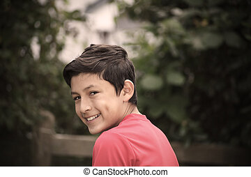 Vintage stylistic portrait of smiling boy with de-saturated...