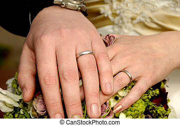 Wedding hands - Two wedding hands with rings and flowers.