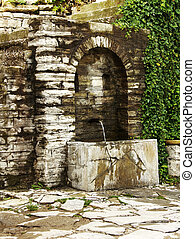 Old water source on street in historic part of Veliko...