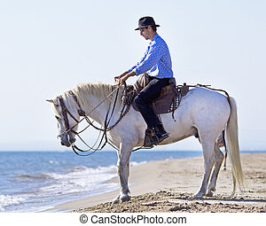 herdsman on the beach - herdsman and Camargue walking in the...