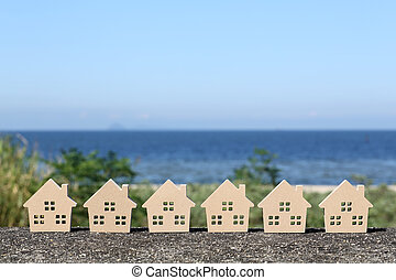 wooden toy house with blue sea and sky background