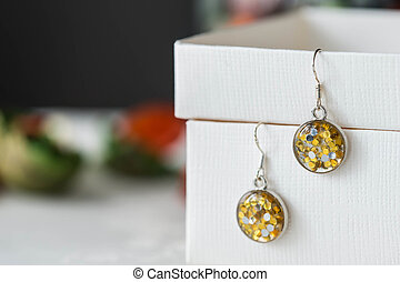 Handmade earrings made of epoxy resin and yellow glitter...