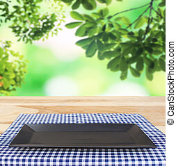 black dish on checkered tablecloth and blur leaves...