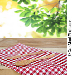 spoon with fork on checkered tablecloth and blur leaves...