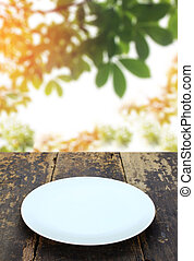 dish on old wood table and blur leaves background