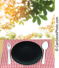 spoon with fork and dish on checkered tablecloth and blur...