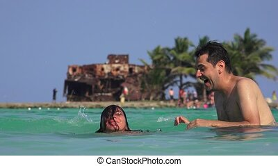 Man And Woman Having Fun Playing In Water On Summer Vacation