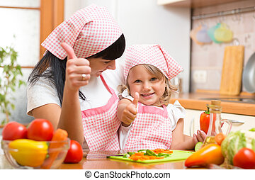 Happy mother and child daughter with fresh vegetables showing thumbs up. Shot in the kitchen
