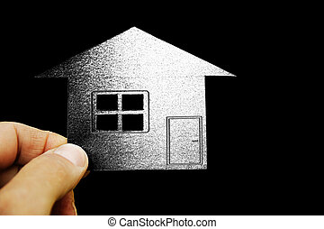 paper house in hands on a background of property