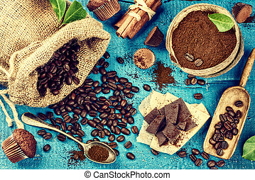 Food background with roasted coffee beans, cinnamon sticks, cupcakes and chocolate