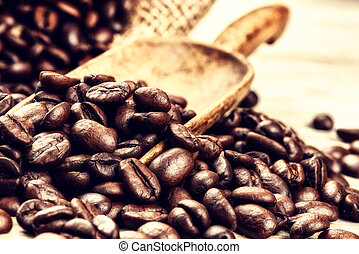 Roasted coffee beans with old wooden scoop