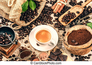 Cup of hot black coffee with old wooden mill grinder and burlap sack with roasted coffee beans