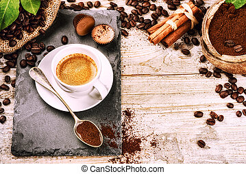 Cup of hot black coffee in setting with roasted coffee beans