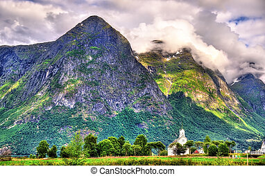 View of white wooden Oppstryn Church and mountains in Norway...