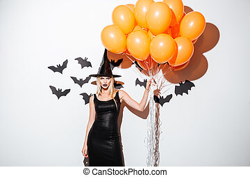 Sexy young woman in witch halloween costume holding orange balloons
