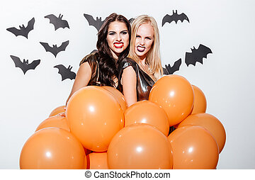 Frightening women with halloween makeup holding balloons and...