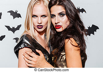 Two beautiful young women with halloween makeup standing...