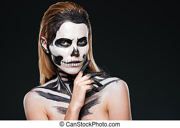 Young woman with gothic skeleton makeup over black...