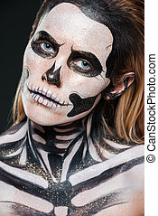 Closeup of woman with scared gothic makeup over black...