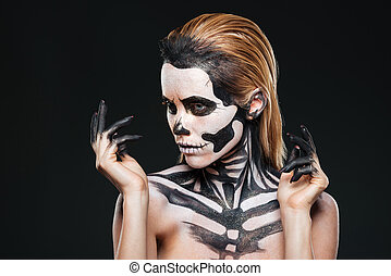 Portrait of girl with fearful halloween makeup over black...