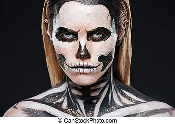 Closeup of young woman with terrifying skeleton makeup over...