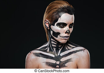 Portrait of woman with intimidating halloween makeup over...