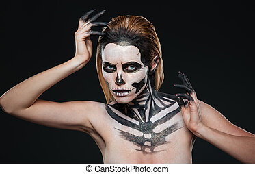 Woman with gothic terrifying makeup posing over black...