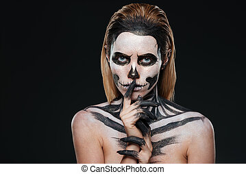 Woman with scared halloween makeup showing silence gesture...
